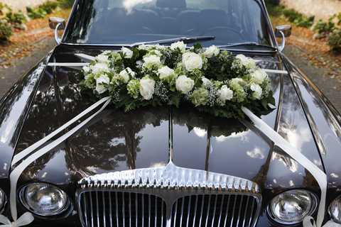 decorate newlyweds car - floral arrangement on hood of car