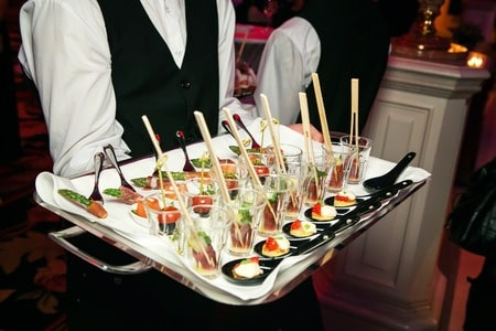 server holding a tray of appetizers