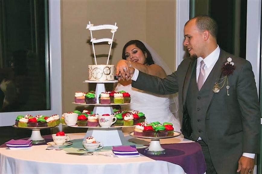 bride and groom cutting wedding cake with cupcakes