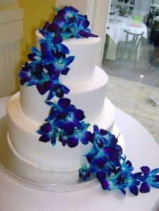 white cake with blue orchids