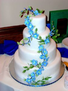 white fondant cake with blue gumpaste flowers